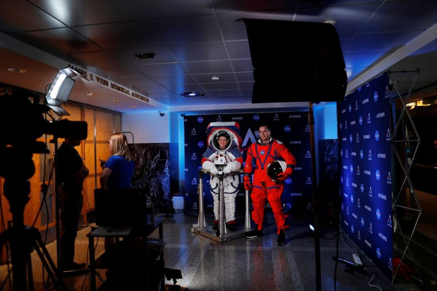 Advanced Space Suit Engineer at NASA Kristine Davis wears the xEMU space suit next to lead engineer Dustin Gohmert wearing the Orion crew survival spacesuit prototype for the next astronaut to the moon by 2024, during a presentation at NASA headquarters in Washington, U.S., October 15, 2019. REUTERS/Carlos Jasso